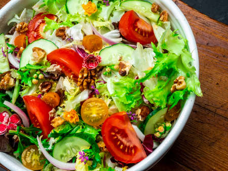 Salad of different types of lettuce, tomato, onion, cucumber and nuts.