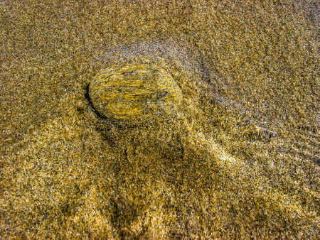 Stone submerged on the shore of the beach, in Marbella, Andalucia, Spain.