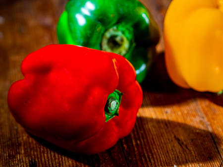 Still life of peppers in three colours on wood Foto de archivo - 150562107