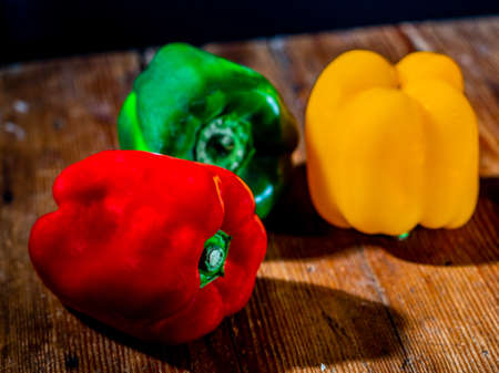 Still life of peppers in three colours on wood