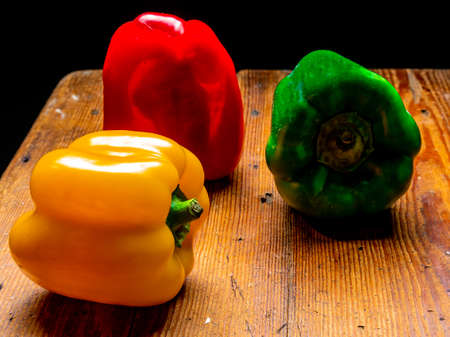 Still life of peppers in three colours on wood Foto de archivo - 150562177