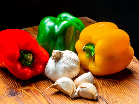 Still life of peppers in three colours on wood Foto de archivo - 150562044