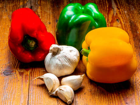 Still life of peppers in three colours on wood Foto de archivo - 150562539