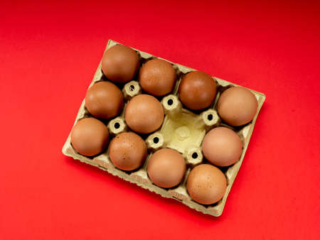 Eggs in a yellow cardboard egg cup on a red background