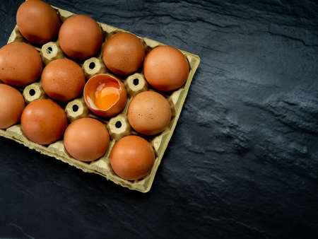 Eggs in a yellow cardboard egg cup on a black background Foto de archivo