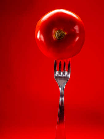 Spiked tomato on a fork with red background