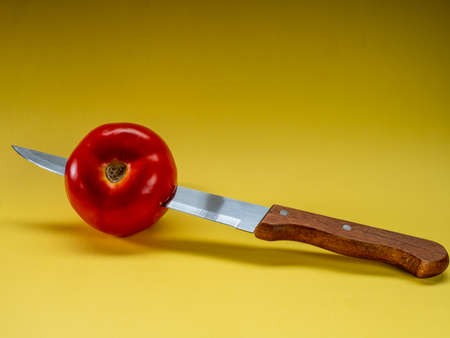 Tomato stuck with a knife
