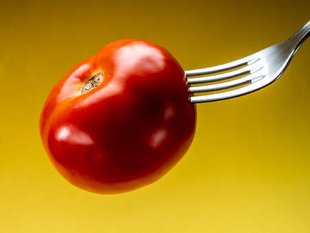 Spiked tomato on a fork with yellow background