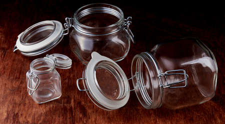 Empty glass jars with open lids are held in place with a metal wire.