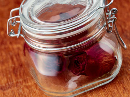 Glass jar filled with dried roses inside