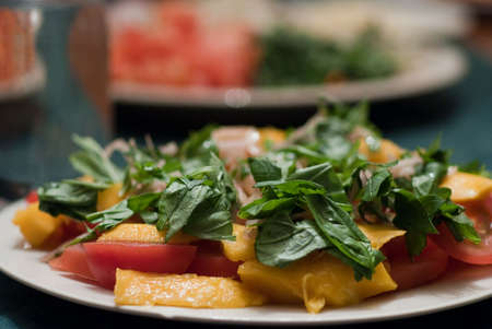 Green salad served with mango and tomatoes photo