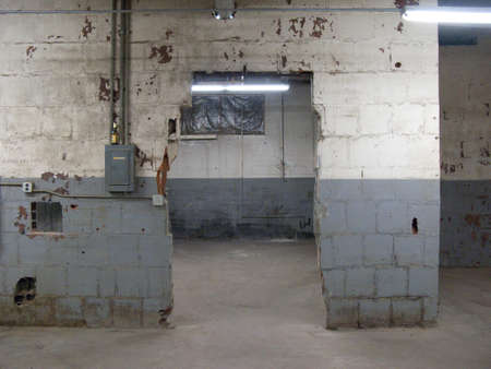 abandoned warehouse: Empty older warehouse  industrial space with grey  white walls