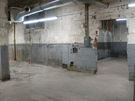 down lights: Empty older warehouse  industrial space with grey  white walls