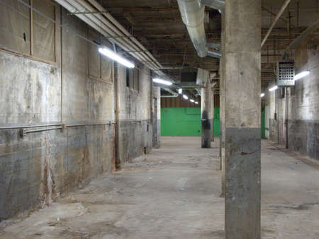 disarray: Empty older warehouse  industrial space with grey  white walls