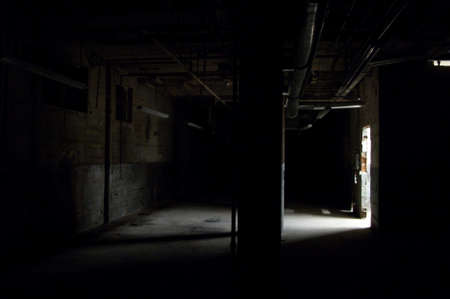 Dark empty warehouse  commercial space with shaft of light