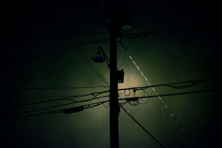 Telephone pole and wires silhouetted against the moon photo