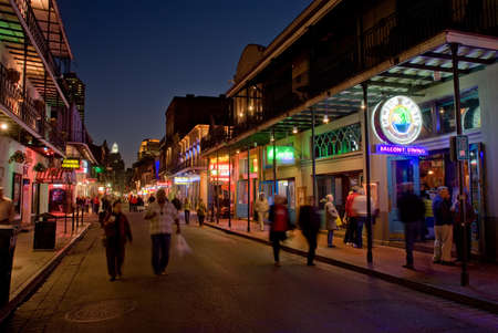 quarter: NEW ORLEANS, USA - CIRCA MARCH 2008: Crowds of people walking down Bourbon Street past the Cajun Cabin bar at dusk circa March 2008 in New Orleans, USA Editorial