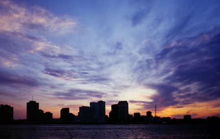 New Orleans city skyline silhouetted against a blue sunset