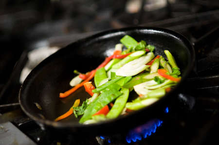 tossing: Chef tossing vegetables in a commercial kitchen Stock Photo