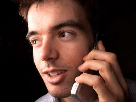 black backgound: Young man talking on a cell phone, black backgound
