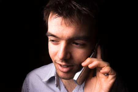 Young man talking on a cell phone, black backgound photo
