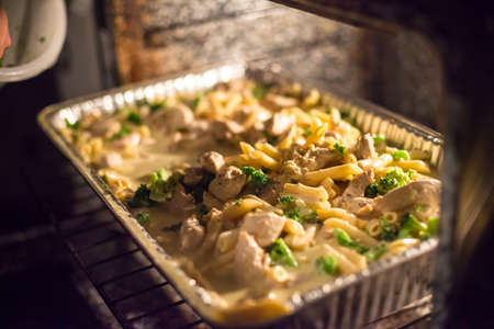 checking ingredients: Chicken, macaroni, broccoli, and cheese in the oven Stock Photo