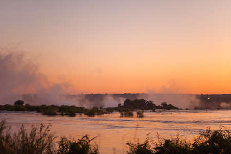 Plume of mist rising from Victoria Falls at sunset photo