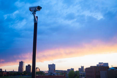 Urban security video camera outdoors at sunset photo