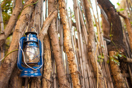 Oil lantern hanging against stick wall in African village photo