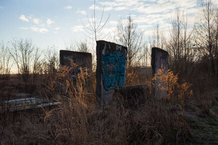 Abandoned concrete structures covered with graffiti at dawn