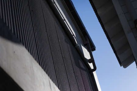 corrugated steel: Downspout and gutters of building with corrugated steel walls