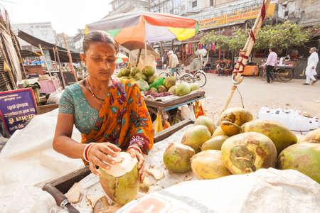 VARANASI, INDIA - 26 Oct 2016: Woman selling coconut milk at Dasaswamedh Ghat opens a coconut on October 26, 2016 in Varanasi, India