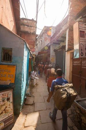 passerby: VARANASI, INDIA - 25 Oct 2016: Passerby walk through the alleyways on October 25, 2016 in Varanasi, India Editorial