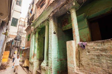 benares: VARANASI, INDIA - 26 Oct 2016: Man walks down back alleyways on October 26, 2016 in Varanasi, India