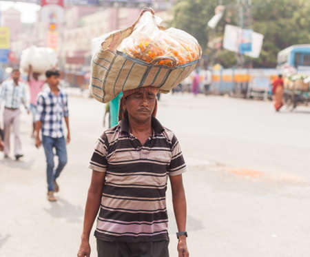 downtrodden: KOLKATA, INDIA - 22 Oct 2016: A man carries a basket of flowers balanced on his head near Howrah Station on October 22, 2016 in Kolkata (Calcutta), India