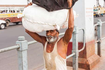 howrah: KOLKATA, INDIA - 22 Oct 2016: A man carries a load on his head across the Howrah Bridge on October 22, 2016 in Kolkata (Calcutta), India