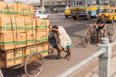 howrah: KOLKATA, INDIA - 22 Oct 2016: Men push a load of apples across the Howrah Bridge on October 22, 2016 in Kolkata (Calcutta), India