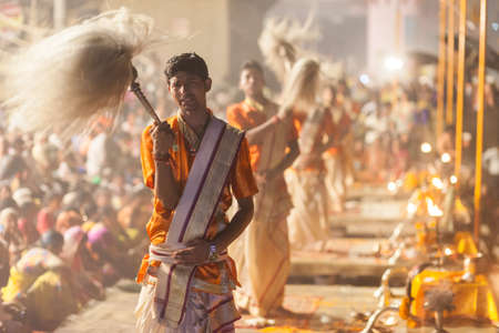 VARANASI, INDIA - 24 Oct 2016: Waving the yak-tail fan. Crowds watch as priests perform the Ganga Aarti ceremony at Dasaswamedh Ghat on October 24, 2016 in Varanasi, India