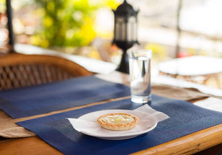 Lemon tart with custard filling and lemon slices on a white plate, blue mat, and wood cafe table