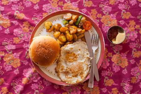butterfly knife: Breakfast plate with egg, toasted buns, fried potatoes, butter and jam in Nepal Stock Photo