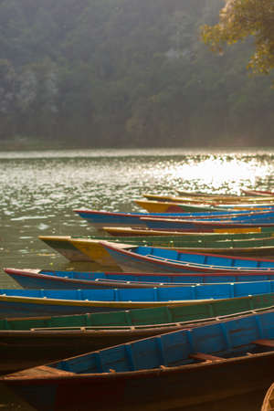 phewa: Rowboats lined up at Fewa Lake (Phewa Tal), Pokhara, Nepal with Machhapuchre in the background Stock Photo