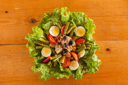 A French Salade Nicoise salad on a wooden table