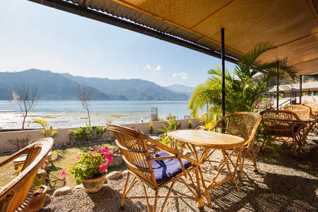 phewa: Wooden cafe table with a view of Fewa (Phewa) Lake on a sunny afternoon in Pokhara, Nepal Stock Photo