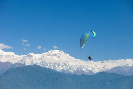 Parapentes tándem flotan sobre Nepal con el Annapurna Himalaya al fondo Foto de archivo