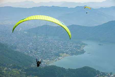 Paragliders float over Pokhara, Nepals Fewa Lake and Lakeside tourist area