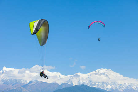 Tandem paragliders float over Nepal with the Annapurna Himalayas in the background