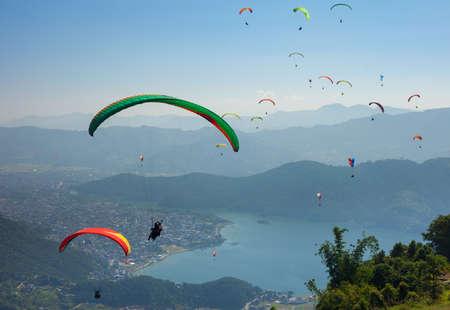Gleitschirmflieger schweben über Pokhara, den Fewa-See in Nepal und das Touristengebiet Lakeside