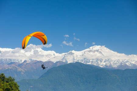Les parapentes tandem flottent au-dessus du Népal avec l'Himalaya de l'Annapurna en arrière-plan
