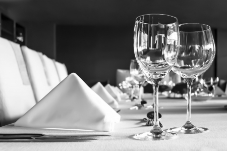 Black and white shot of a table setting with wineglasses, white napkins and silwerware on white tablecloth.