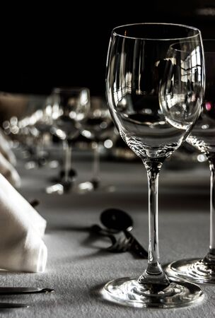 Black and white shot of a table setting with wineglasses, white napkins and silwerware on white tablecloth. photo